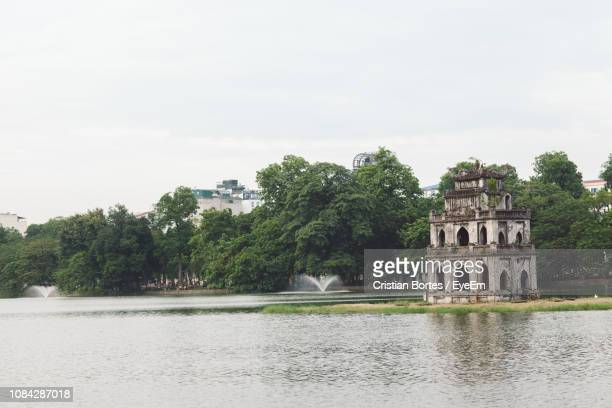 view of abandoned building at lake against sky - bortes stock pictures, royalty-free photos & images