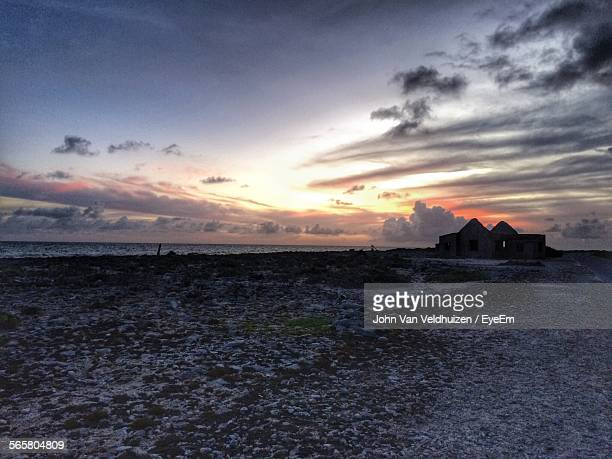 View Of Abandoned Building On Coast Against Cloudy Sky At Sunset