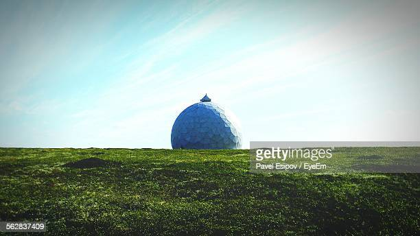 View Of Abandoned Radar Station On Grassy Landscape Against Cloudy Sky