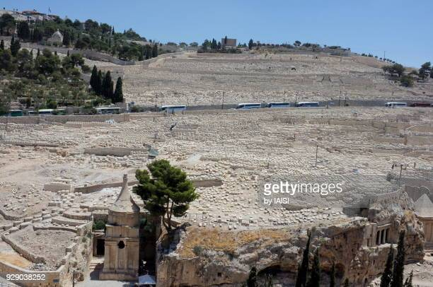 a view of absalon's tomb in the kidron valley, and the jewish cemetery on mount of olives with its thousands jewish tombs - mount of olives stock photos and pictures