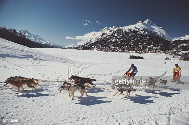 View of action in a sled dog race with two competitors riding on sleds being pulled by husky like dogs at St Moritz in Switzerland in 1990