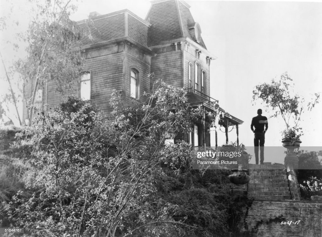 View of actor Anthony Perkins standing beside the Bates Motel in a still from the film, 'Psycho,' directed by Alfred Hitchcock, 1960.