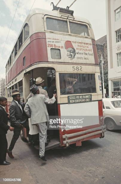 View of African men boarding a segregated nonEuropean trolley bus at a bus stop on a main road in the centre of Johannesburg during the Apartheid era...