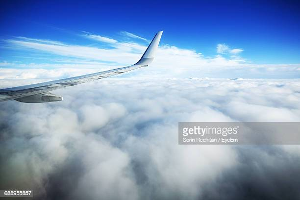 View Of Airplane Wing And Clouds In Sky