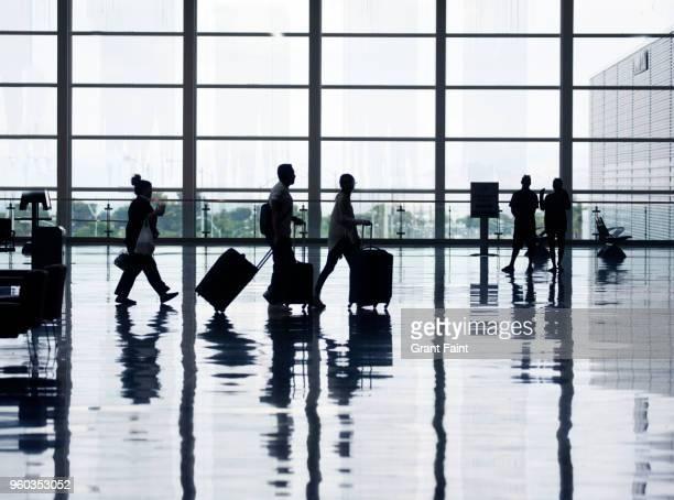 view of airport departures area travellers rushing. - toerist stockfoto's en -beelden