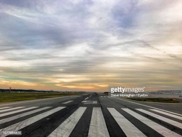 view of airport runway against sky during sunset - airport runway stock pictures, royalty-free photos & images