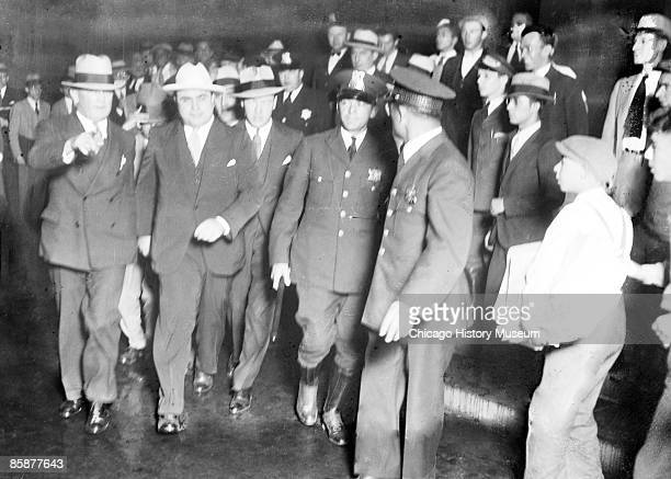 View of Al Capone striding along escorted by police and unidentified men around the time of his trial, Chicago, 1931.