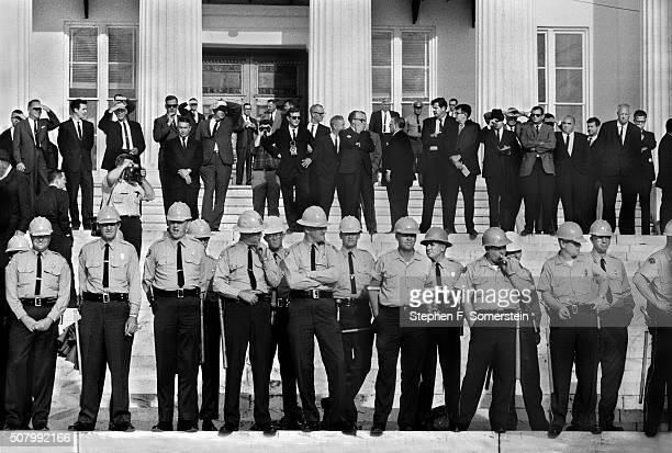 A view of Alabama state police and onlookers on the steps of the Montgomery Alabama State House at the end of the Selma To Montgomery Civil Rights...