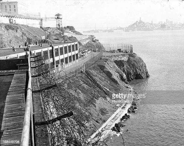 View of Alcatraz island taken from the industrial area with a guard tower, main cellhouse and skyline in the background, San Francisco, California,...