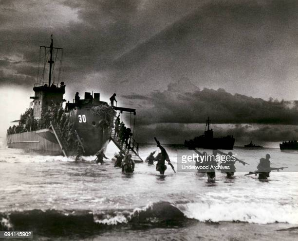 View of Allied troops from a transport vessel, among them medics with stretchers over their shoulders, as they wade ashore during the invasion of...