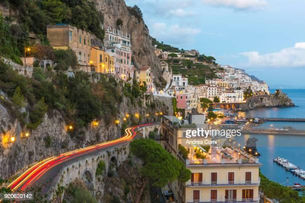 View of Amalfi village and coastline at dusk. Amalfi, Amalfi coast, Salerno, Campania, Italy