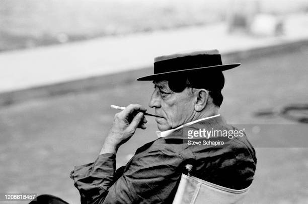 View of American actor and comedian Buster Keaton a cigarette holder in his hand as he sits in a director's chair during the filming of his movie...