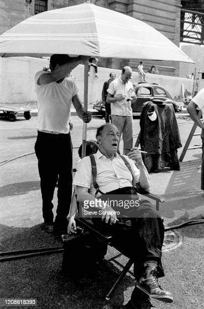 View of American actor and comedian Buster Keaton with a cigarette holder in his hand as he sits under an umbrella in a director's chair during the...