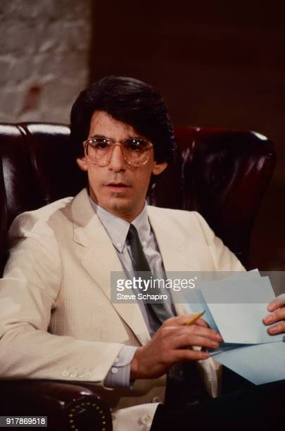 View of American actor and comedian Richard Belzer as he sits in an armchair a collection of notecards in his hands Los Angeles California 1983