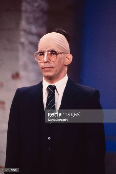 View of American actor and comedian Richard Belzer in a bald cap as he performs during an skit Los Angeles California 1983
