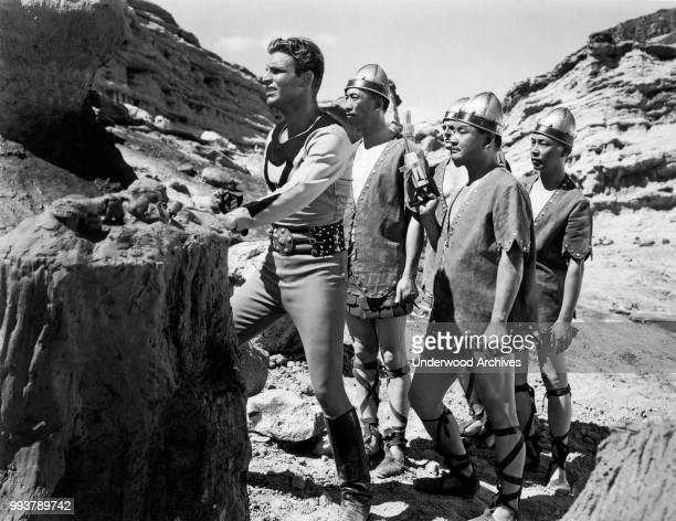 View of American actor Buster Crabbe in costume as the title character in the serial 'Buck Rodgers' along with unidentified cast members Hollywood...