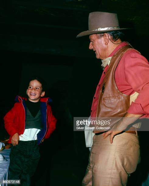 View of American actor John Wayne hands on his hips as he looks at his son John Ethan who copies his father's pose in an unspecified restaurant 1967...