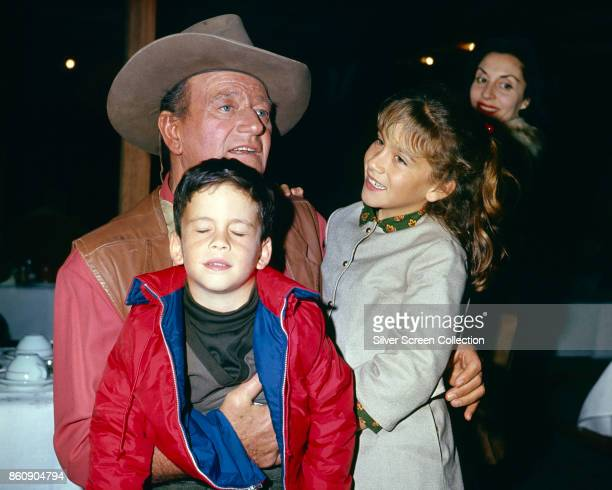View of American actor John Wayne with two of his children, son John Ethan and daughter Aissa Wayne, and, in the background, his wife, Peruvian-born...