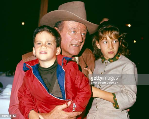View of American actor John Wayne with two of his children, son John Ethan and daughter Aissa Wayne, as they are photographed in an unspecified...