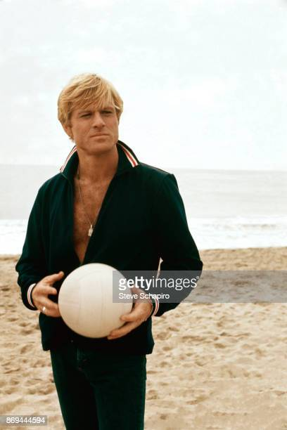 View of American actor Robert Redford as he holds a vollyball on the beach on the set of the film 'The Way We Were' Los Angeles California 1972