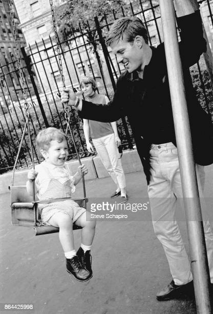 View of American actor Robert Redford as he pushes his son David on a playground swing in Central Park New York New York 1966