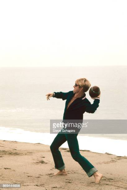 View of American actor Robert Redford as he throws a football on the beach on the set of the film 'The Way We Were' Los Angeles California 1972