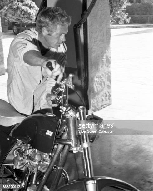 View of American actor Steve McQueen a cigarette in his mouth as he wheels a motorcycle out of his garage Brentwood Los Angeles California 1960s