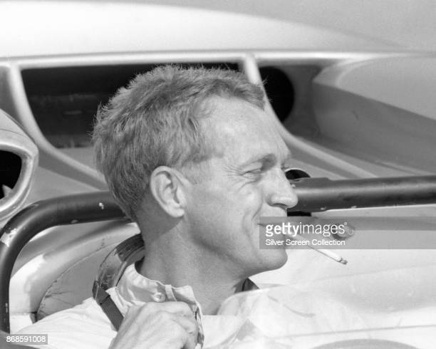 View of American actor Steve McQueen a cigarette in his mouth as he sits in car at Riverside Raceway Riverside California July 1966
