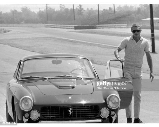 View of American actor Steve McQueen as he stands beside the open door of a Ferrari Lusso 250 Berlinetta, late 1960s.