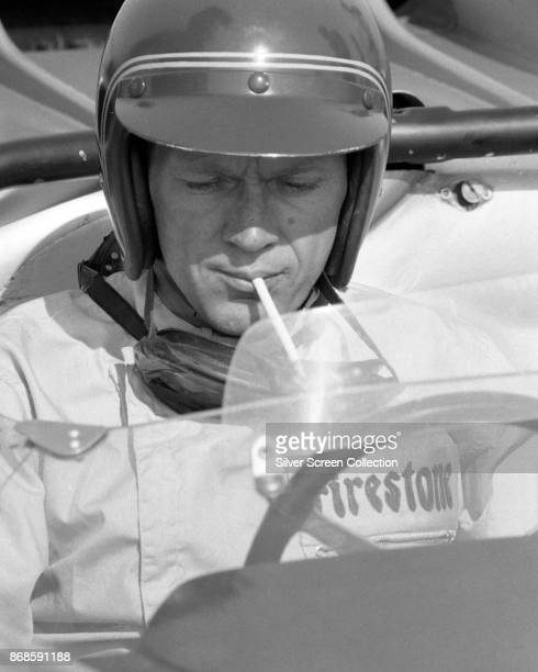 View of American actor Steve McQueen in Firestone racing suit and with a cigarette in his mouth as he sits behind the wheel of a car at Riverside...