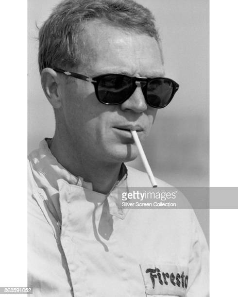 View of American actor Steve McQueen in Firestone racing suit and sunglasses as he smokes a cigarette at Riverside Raceway Riverside California July...