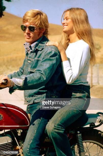 View of American actors Robert Redford and Lauren Hutton both seated on a motorcycle on the set of the film 'Little Fauss and Big Halsy' California...