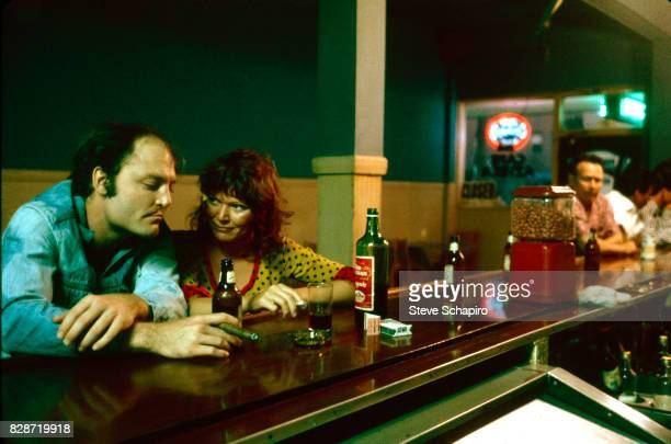 View of American actors Stacy Keach and Susan Tyrell as they sit at a bar in a scene from the film 'Fat City' , Stockton, California, 1972.