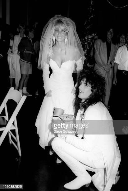 View of American actress Heather Locklear and musician Tommy Lee as the latter adjusts the former's garter during their wedding at the Santa Barbara...