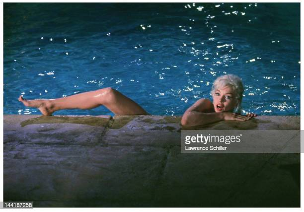 APPLY View of American actress Marilyn Monroe one leg and both arms hooked over the edge of a pool during the filming of 'Something's Got to Give'...
