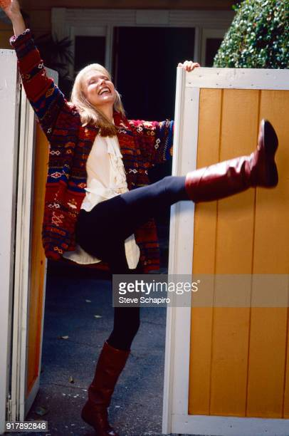 View of American actress Susan Blakely as she kicks out one leg her head tilted back as she stands in an open gateway Los Angeles California 1979