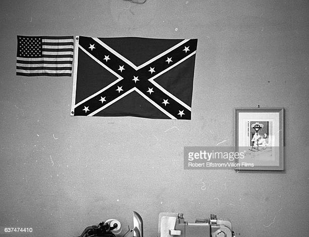 View of American and Confederate flags along with a framed racially stereotyped poster on a wall in City Hall Greenwood Mississippi 1964