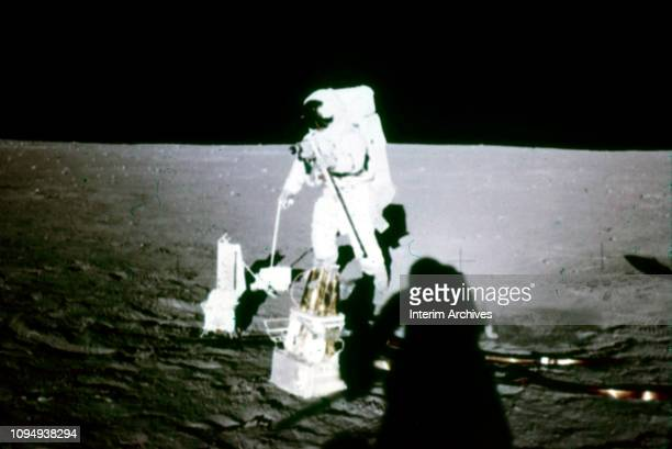 View of American astronaut Alan Bean during NASA's Apollo 12 mission sets up a camera on the surface of the moon November 19 1969 The shadow at...