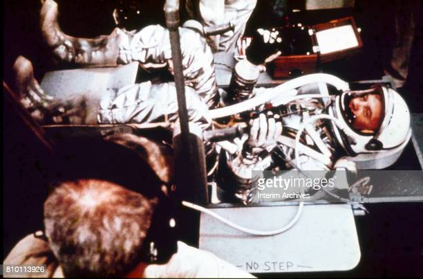 View of American astronaut John Glenn fully dressed in his spacesuit and seated in a command seat mockup as an unidentified technician performs a...