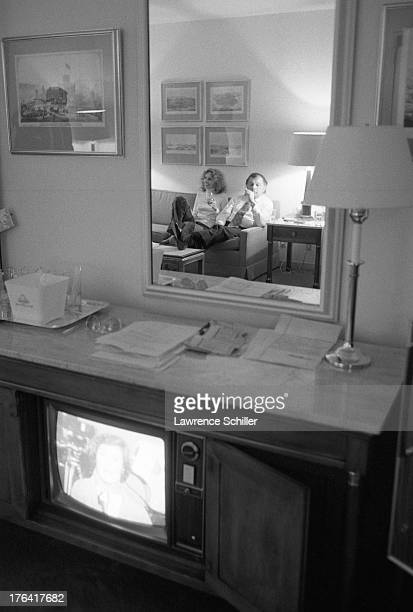View of American attorney F Lee Bailey and his wife Lynda Hart both reflected in the mirror as they watch television in their room at the Stanford...