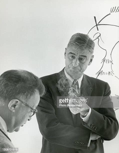 View of American author Theodor Seuss Geisel , known as Dr Seuss, as he smokes a cigarette while speaking with American critic and author Clifton...