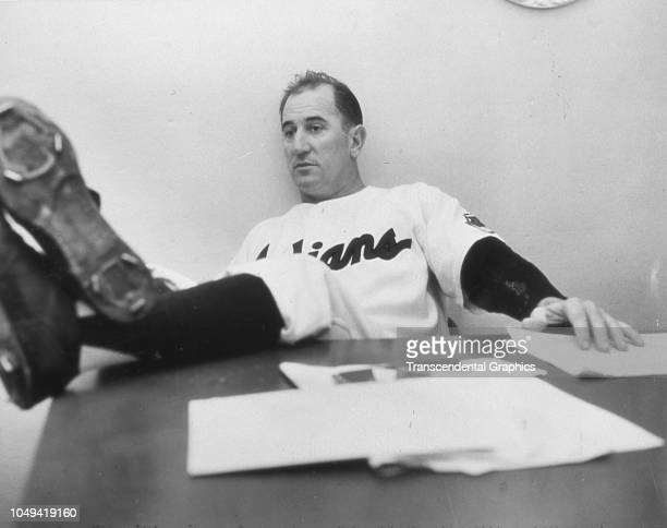 View of American baseball manager Al Lopez , of the Cleveland Indians, as he sits with his feet on his desk, in his office at Municipal Stadium,...