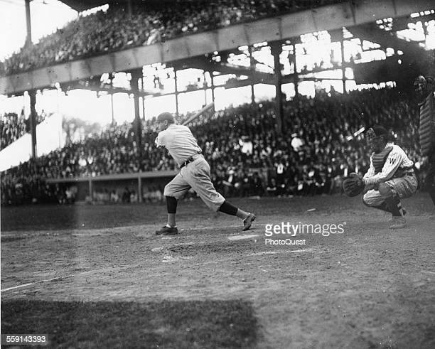 View of American baseball player Babe Ruth as he swings at a pitch 1920s