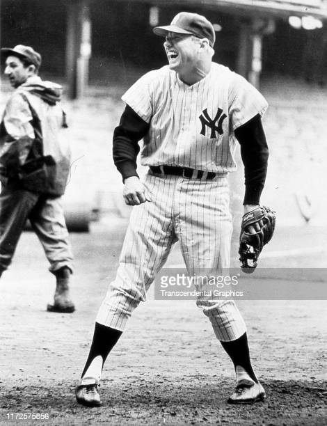 View of American baseball player Mickey Mantle of the New York Yankees as he laughs while on the field before a game at Yankee Stadium New York New...