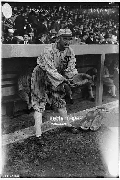 View of American baseball player Shoeless Joe Jackson of the Chicago White Sox as he poses as a catcher beside his team's dugout 1917