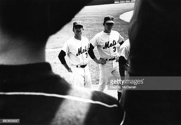 View of American baseball players Bud Harrelson and Ray Sadecki both of the New York Mets and seen over between the shoulders of a pair of fans as...