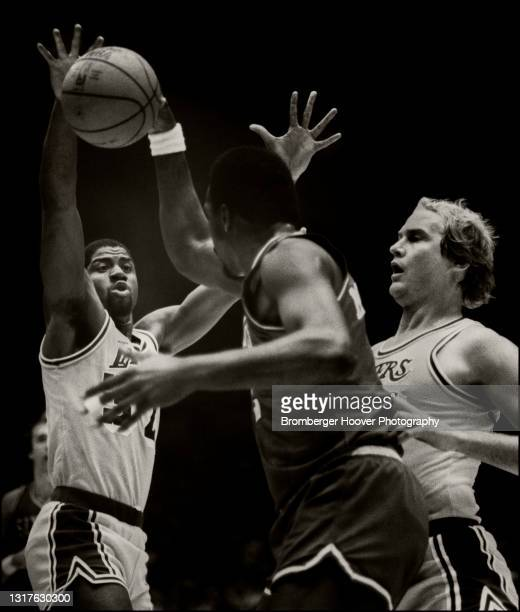 View of American basketball player Magic Johnson , of the Los Angeles Lakers, as he defends against Moses Malone , of the Philadelphia 76ers, during...
