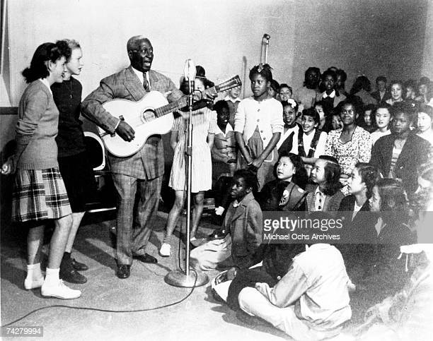 View of American Blues musician Lead Belly as he plays guitar for an audience of mostly children, 1940s.