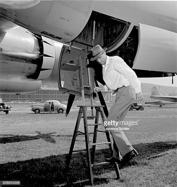 View of American businessman and aviator Howard Hughes on a stepladder beneath one of his airplanes, Los Angeles, California, 1947.