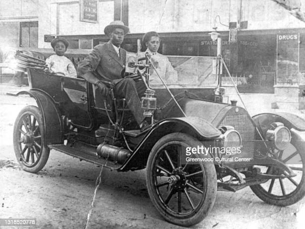 View of American businessman John Wesley Williams sits in his car with wife Loula Williams and their son, WD Williams, Tulsa, Oklahoma, 1910s.